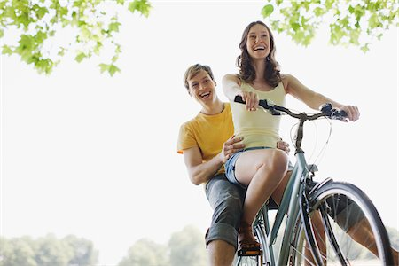Smiling woman riding boyfriend on bicycle Stock Photo - Premium Royalty-Free, Code: 635-03685199