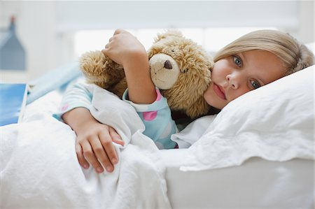 Sick girl laying in bed with teddy bear Stock Photo - Premium Royalty-Free, Code: 635-03685284