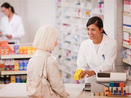 Pharmacist handing medication to customer in drug store Stock Photo - Premium Royalty-Free, Code: 635-03685283