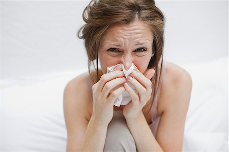 Sick woman in bed blowing nose Stock Photo - Premium Royalty-Free, Code: 635-03685296