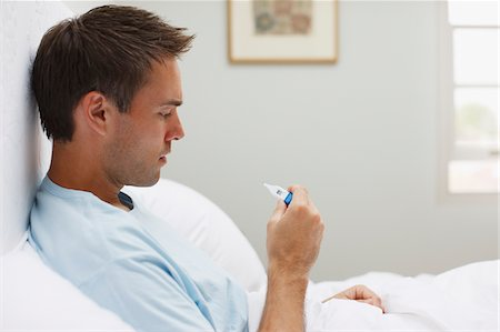 Sick man taking temperature with digital thermometer Stock Photo - Premium Royalty-Free, Code: 635-03685291
