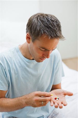 dubious - Man holding pills and counting them Stock Photo - Premium Royalty-Free, Code: 635-03685311
