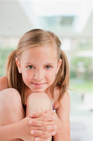 Smiling girl with bandage on knee Stock Photo - Premium Royalty-Free, Code: 635-03685345