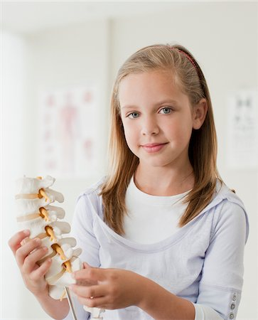 Girl holding model of spine in doctor's office Stock Photo - Premium Royalty-Free, Code: 635-03685367
