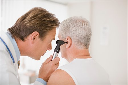 Doctor examining patient's ear in doctor's office Stock Photo - Premium Royalty-Free, Code: 635-03685377