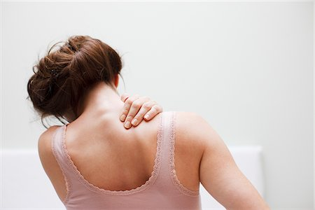 Woman rubbing aching back Stock Photo - Premium Royalty-Free, Code: 635-03685390