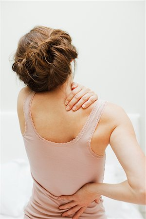 Woman rubbing aching back Stock Photo - Premium Royalty-Free, Code: 635-03685391