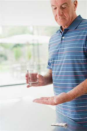 Senior man holding glass of water and pills Stock Photo - Premium Royalty-Free, Code: 635-03685403