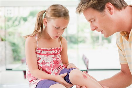 Father tending to daughter's scraped knee Stock Photo - Premium Royalty-Free, Code: 635-03685410