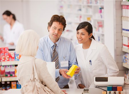 Pharmacists answering questions for customer in drug store Stock Photo - Premium Royalty-Free, Code: 635-03685423