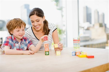 Mother watching son stacking alphabet blocks and spelling 'home' Stock Photo - Premium Royalty-Free, Code: 635-03685443