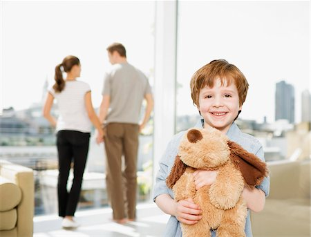 renting - Boy holding stuffed dog with parents in background Stock Photo - Premium Royalty-Free, Code: 635-03685459