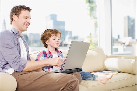 renting - Father and son using laptop in living room Stock Photo - Premium Royalty-Free, Code: 635-03685478
