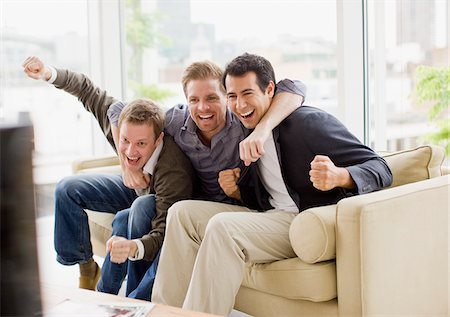 Cheering friends watching television Stock Photo - Premium Royalty-Free, Code: 635-03685546
