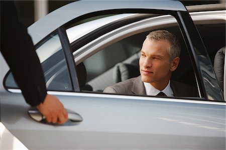 superior - Chauffeur opening car door for businessman Stock Photo - Premium Royalty-Free, Code: 635-03685585