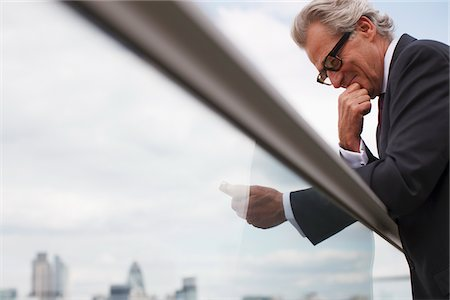 dubious - Businessman leaning on balcony railing using cell phone Stock Photo - Premium Royalty-Free, Code: 635-03685586