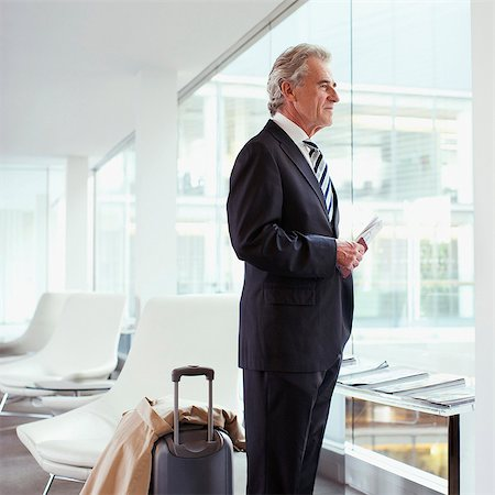 Businessman standing with passport and luggage in airport Stock Photo - Premium Royalty-Free, Code: 635-03685608