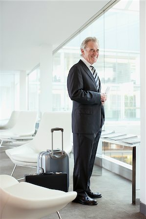 Businessman standing with passport and luggage in airport Stock Photo - Premium Royalty-Free, Code: 635-03685609