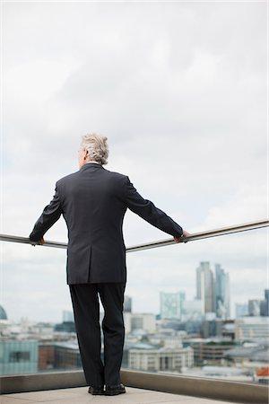 Businessman standing on urban balcony Stock Photo - Premium Royalty-Free, Code: 635-03685600