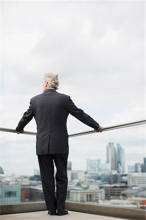 Businessman standing on urban balcony Stock Photo - Premium Royalty-Free, Code: 635-03685600