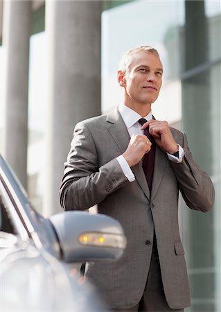 Businessman adjusting necktie outdoors Stock Photo - Premium Royalty-Free, Code: 635-03685657