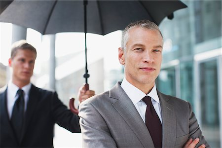 superior - Chauffeur holding umbrella for businessman Stock Photo - Premium Royalty-Free, Code: 635-03685676