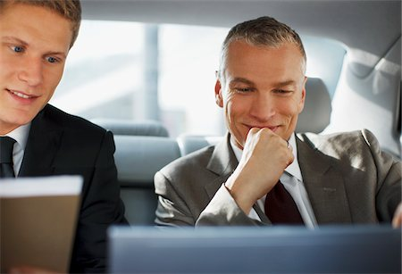 Businessmen working in back seat of car Stock Photo - Premium Royalty-Free, Code: 635-03685672