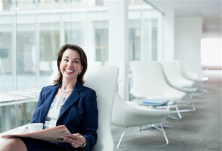 Businesswoman reading newspaper in waiting area Stock Photo - Premium Royalty-Free, Code: 635-03685687