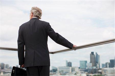 Businessman standing on urban balcony Stock Photo - Premium Royalty-Free, Code: 635-03685699