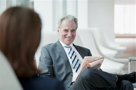 Businessman reading newspaper in waiting area Stock Photo - Premium Royalty-Free, Code: 635-03685690