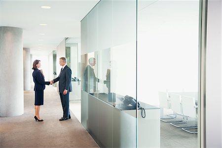 partnership - Business people shaking hands in modern office corridor Stock Photo - Premium Royalty-Free, Code: 635-03685711