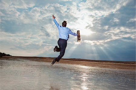 Businessman jumping on beach and looking at sky Stock Photo - Premium Royalty-Free, Code: 635-03685730