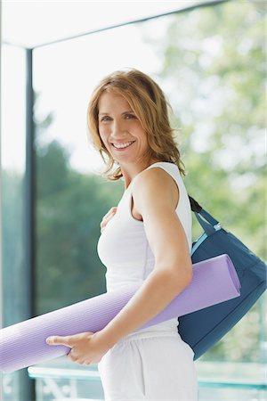 Smiling woman holding yoga mat Stock Photo - Premium Royalty-Free, Code: 635-03716054