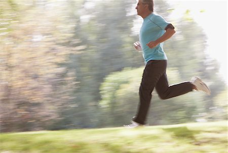 Determined man running outdoors Stock Photo - Premium Royalty-Free, Code: 635-03716107