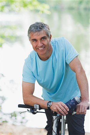 Smiling man standing with bicycle Stock Photo - Premium Royalty-Free, Code: 635-03716101