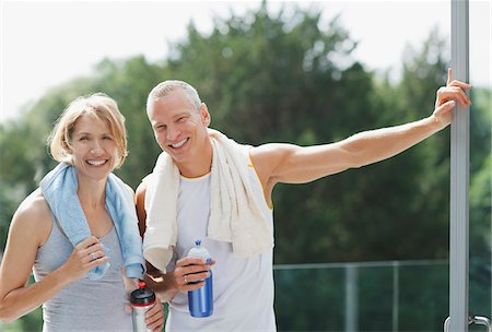 Smiling couple drinking water after exercise Stock Photo - Premium Royalty-Free, Code: 635-03716102