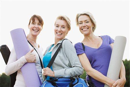 Smiling women holding yoga mats Stock Photo - Premium Royalty-Free, Code: 635-03716113