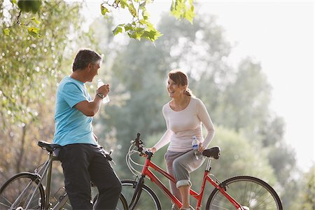 Couple with bicycles drinking water Stock Photo - Premium Royalty-Free, Code: 635-03716124