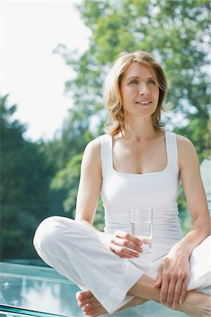 Smiling woman drinking water after exercise Stock Photo - Premium Royalty-Free, Code: 635-03716125