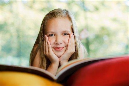 Smiling girl reading book Stock Photo - Premium Royalty-Free, Code: 635-03716144