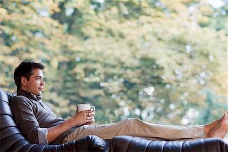 Man reclining in chair drinking coffee Stock Photo - Premium Royalty-Free, Code: 635-03716154