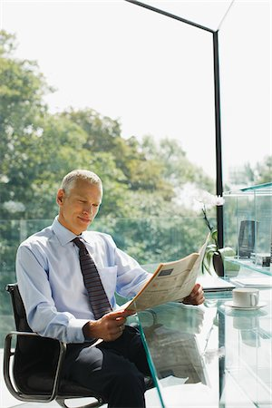 Businessman reading newspaper at desk Stock Photo - Premium Royalty-Free, Code: 635-03716159