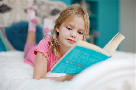 Girl laying on bed reading book Stock Photo - Premium Royalty-Free, Code: 635-03716175