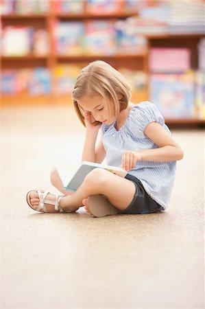 Girl sitting on floor reading book Stock Photo - Premium Royalty-Free, Code: 635-03716183