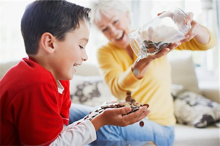 Grandmother emptying jar of coins into grandson's hands Stock Photo - Premium Royalty-Free, Code: 635-03716192