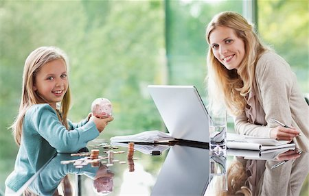 Mother watching daughter count coins from piggy bank Stock Photo - Premium Royalty-Free, Code: 635-03716193