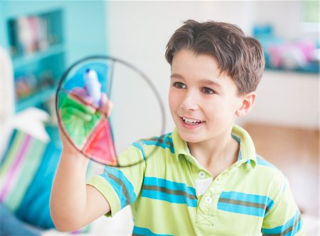 Boy drawing pie chart on glass wall Stock Photo - Premium Royalty-Free, Code: 635-03716208