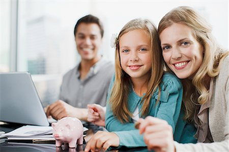 Mother and daughter putting coins into piggy bank Stock Photo - Premium Royalty-Free, Code: 635-03716226