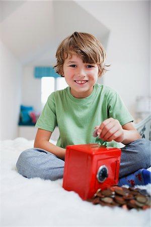 Boy putting coins into safe piggy bank Stock Photo - Premium Royalty-Free, Code: 635-03716220