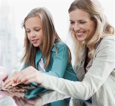 Mother and daughter counting coins Stock Photo - Premium Royalty-Free, Code: 635-03716254